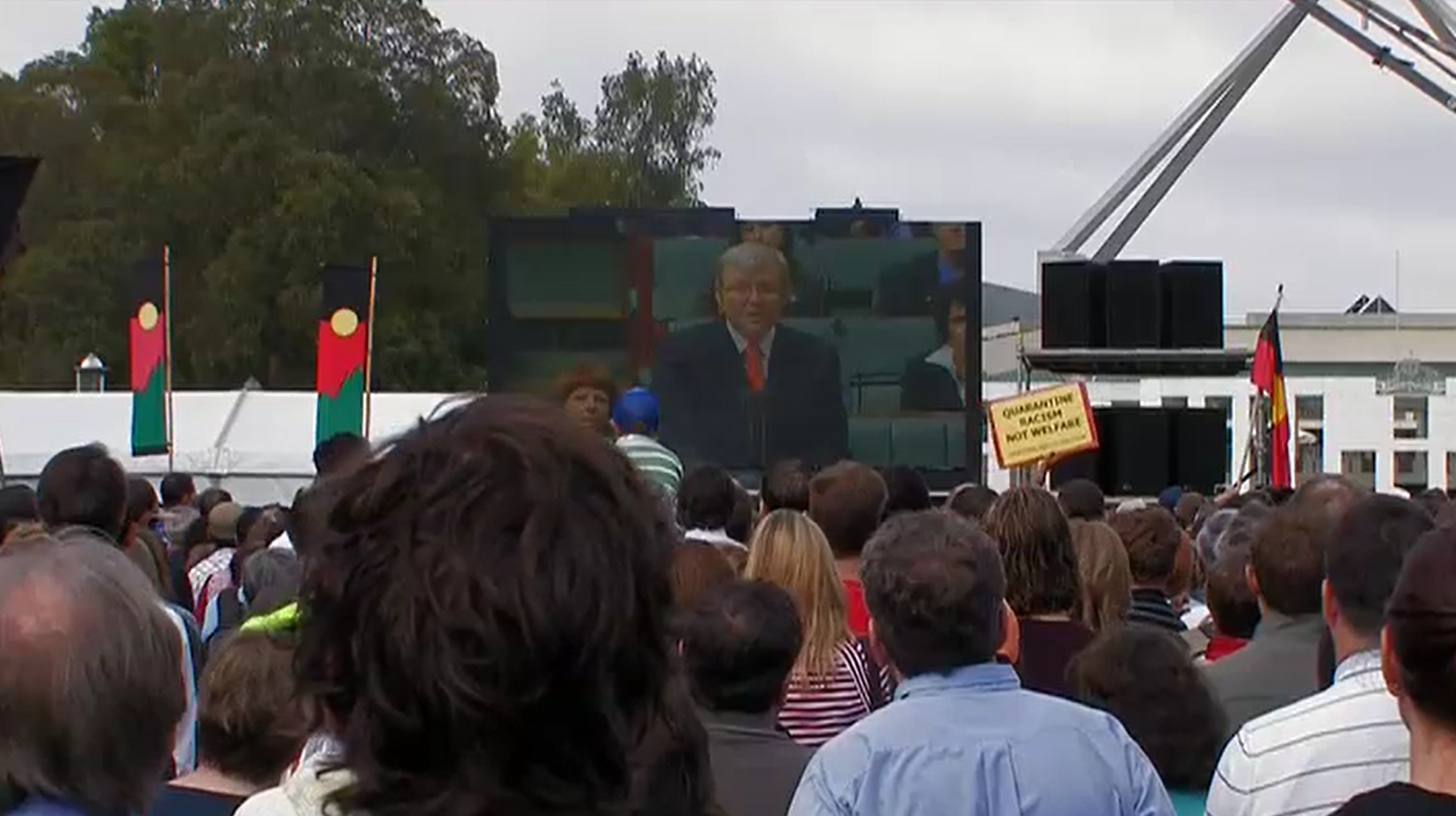 On 13 February 2008 crowds gathered in Australian capital cities to watch Prime Minister Kevin Rudd deliver The Apology to the Stolen Generations live from the House of Representatives at Australian Parliament House. This crowd is watching from the lawns in front of Australian Parliament House. Still from Emily in Japan – The making of an exhibition 2009. Courtesy Ronin Films.