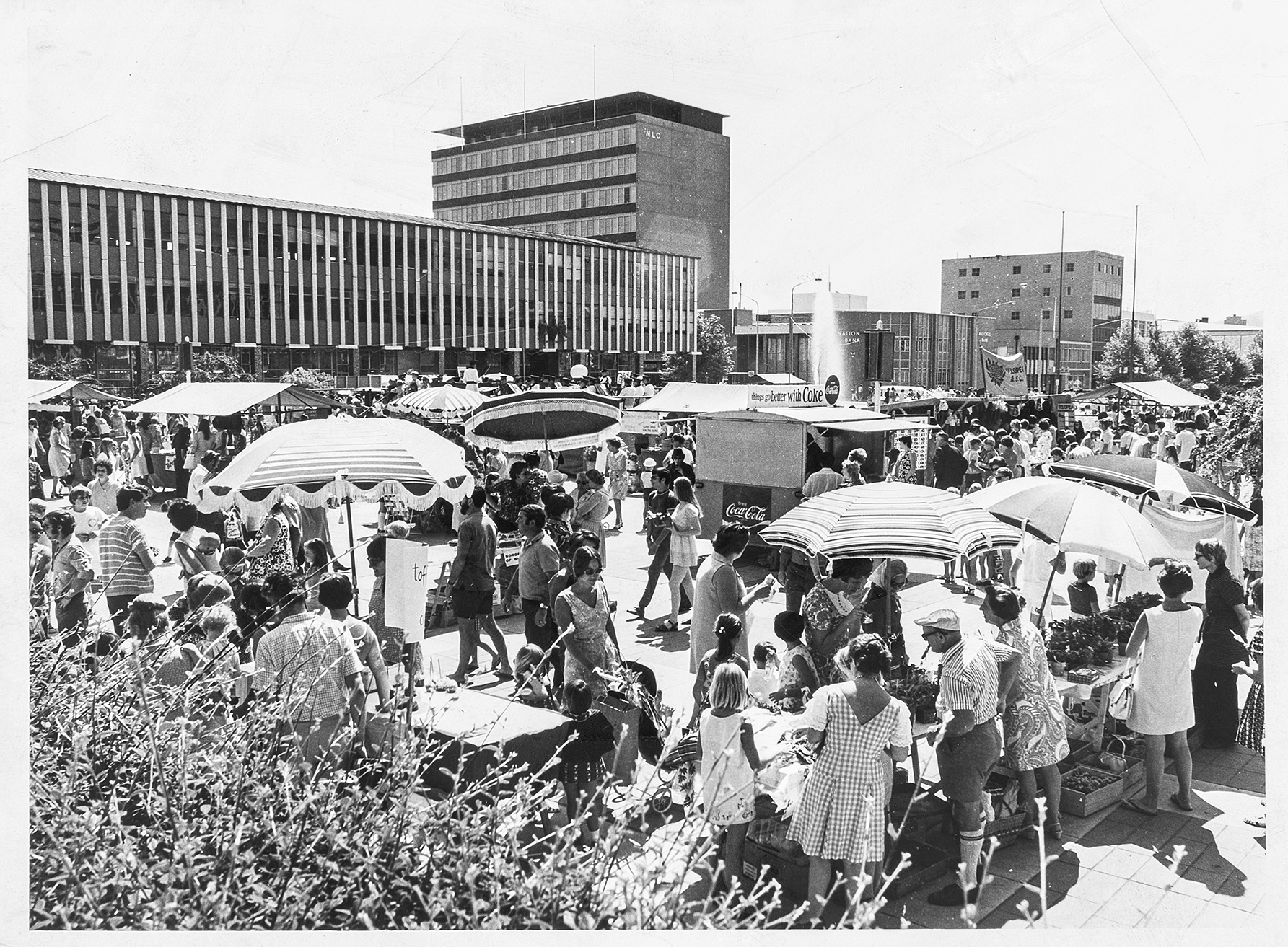 sun umbrellas and a crowd gathered in a town square surrounded by 1960s 'administrative-style' civic architecture.