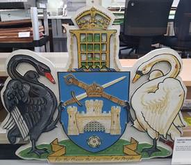 A wooden coat of arms showing a white swan and a black swan facing each other. A sheild showing a castle and cross swords is betwwen them, headed by a portcullis infront of a tree, with a crown on top.